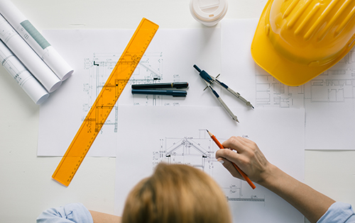 person working on engineering blueprint, tools, hardhat